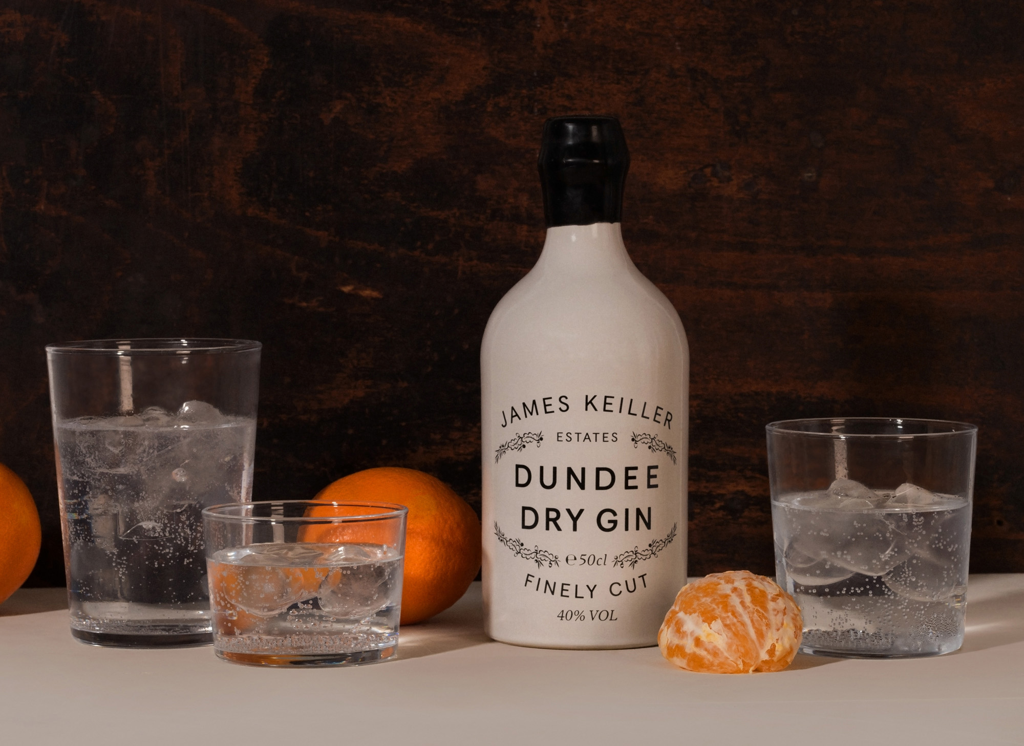 Keillers Dundee Dry Gin with oranges and glasses of liquid and ice